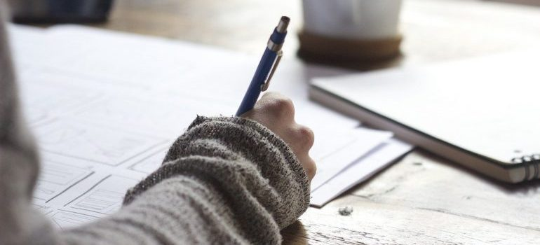 A woman holding a pen and writing.