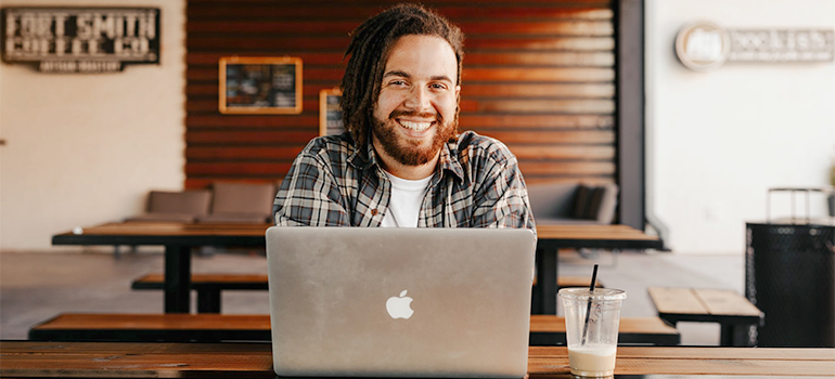 a happy man in front of computer
