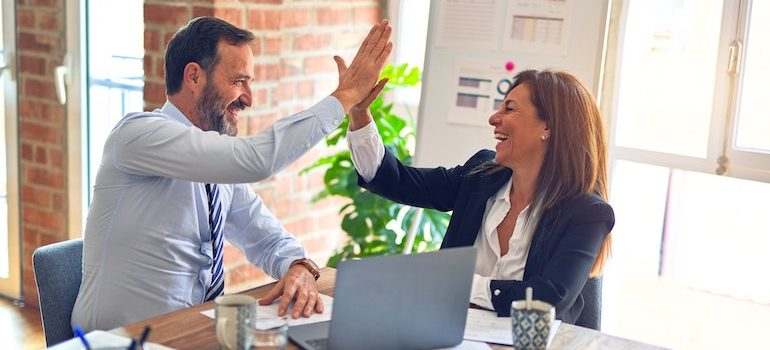 man and a woman high fiving in an office