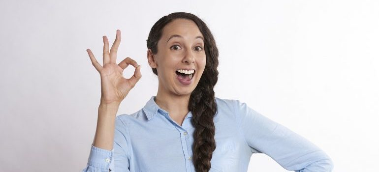Woman holding a-ok sign, excited about upcoming relocation with local movers Aventura.