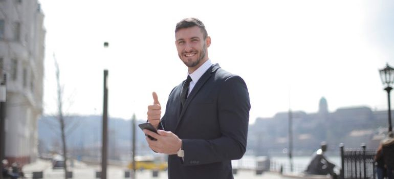 A smiling businessman holding thumbs up for Largo FL commercial movers.