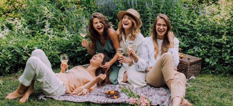 A group of ladies having wine and laughing.
