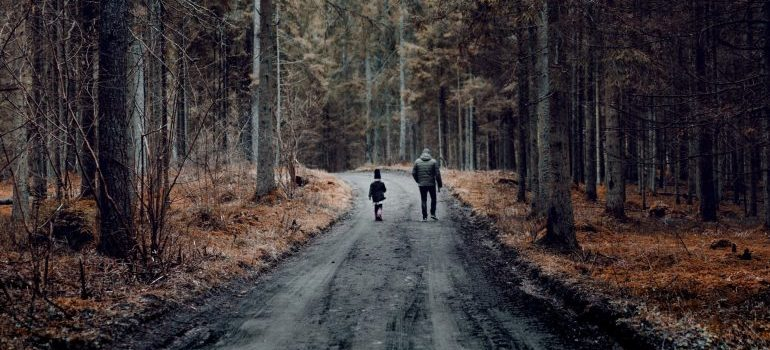 man and boy walking in the woods