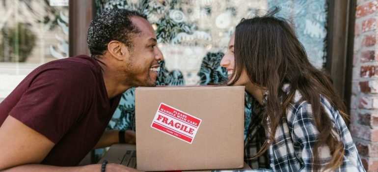 two people leaning on a cardboard box