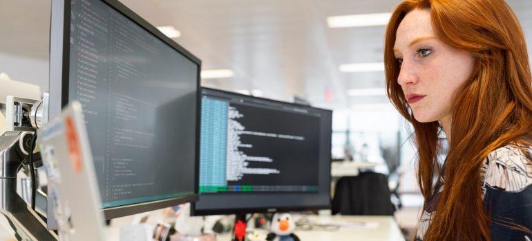 A redhead woman coding.