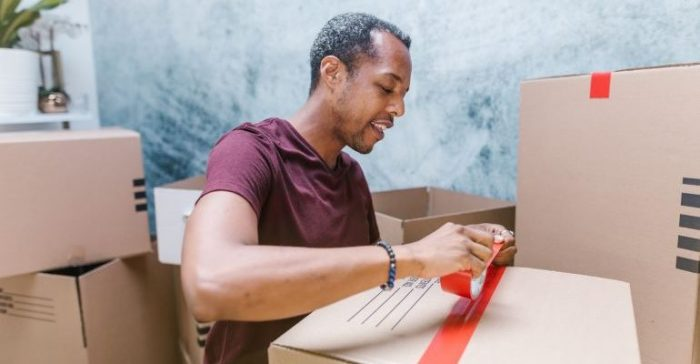 A person taping a moving box.
