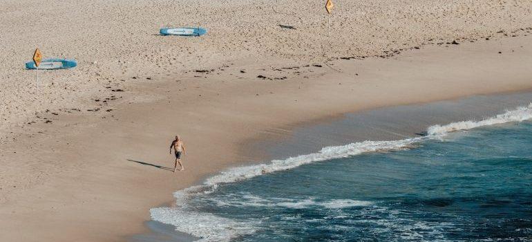 a man walking in swim shorts on beach