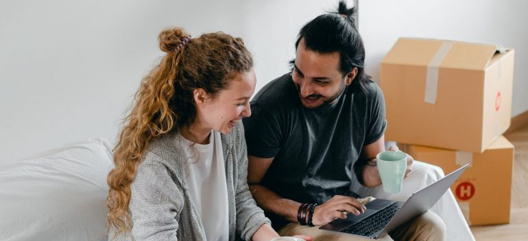A couple laughing over on a laptop