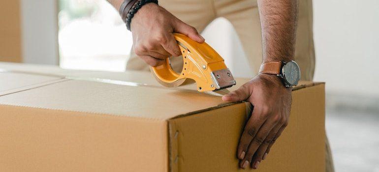 faceless man taping a box