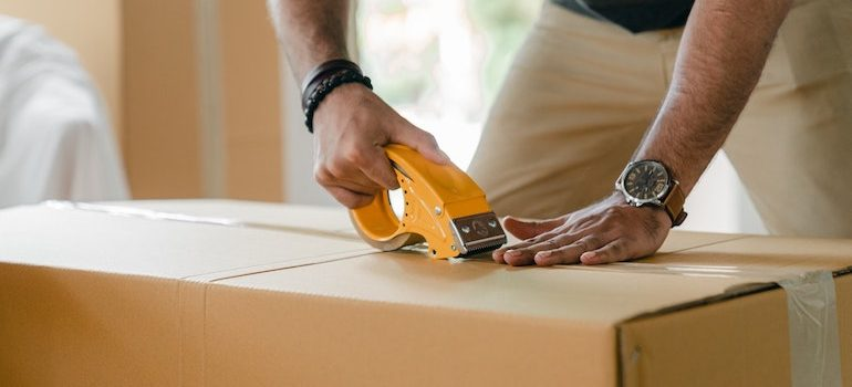 a man taping a box is part of local movers Ormond Beach