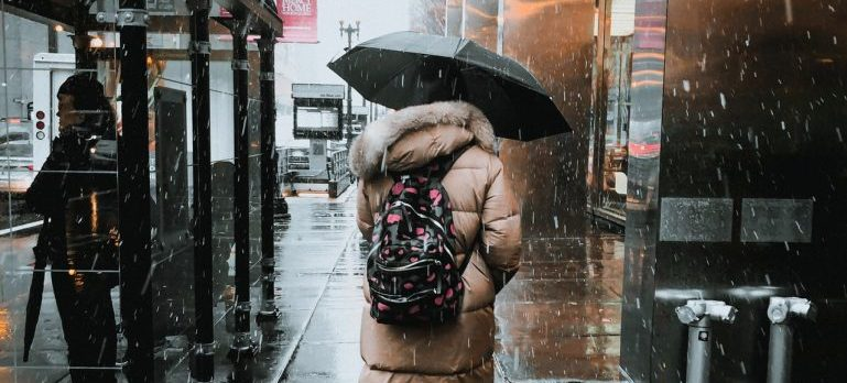 A woman moving in the rain since she didnt know how important it is to choose your moving date wisely.