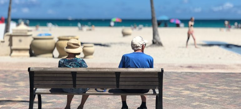 Elder couple sitting on a bench in Miami.
