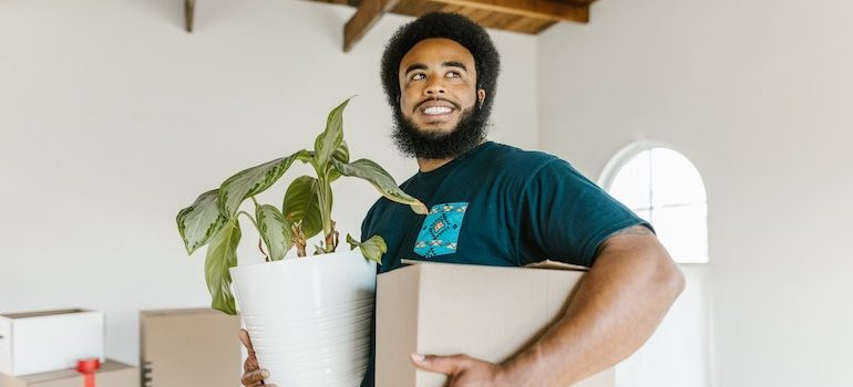 Man holding a box and a plant