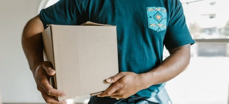 A person carrying a moving box when moving from Orlando to Miami.