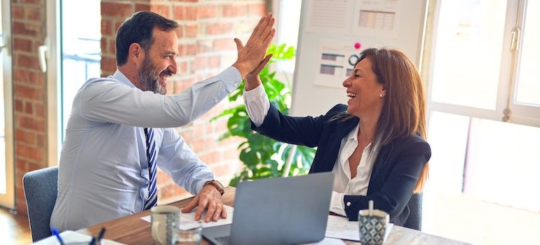 Man and woman in the office high fiving