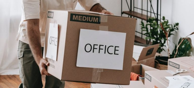 """person carrying a cardboard box labelled """"office"""""""
