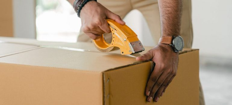 Man sealing moving box before Moving from Lake Worth to Fort Lauderdale