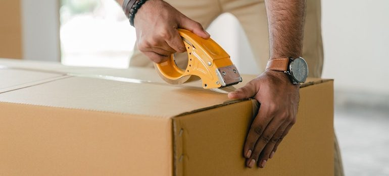 hands taping a box are part of the best movers Gainesville FL