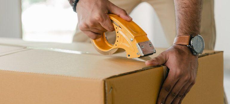 man sealing a box