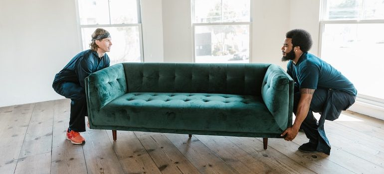 two men lifting a sofa