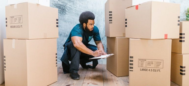 man surrounded by boxes taking notes is part of commercial movers Clearwater