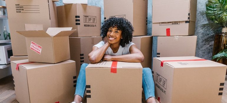 woman sitting on the floor surrounded by boxes