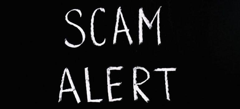 scam alert written in chalk