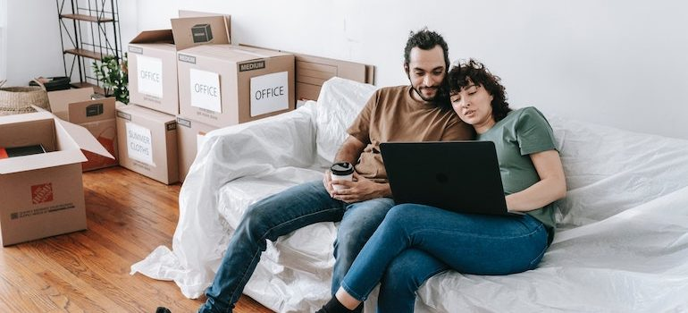 man and woman on a sofa surrounded by boxes looking at computer