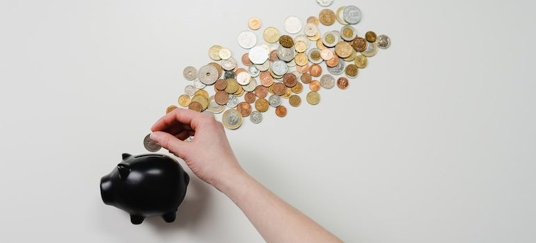 hand putting money into a piggy bank and coins behind it