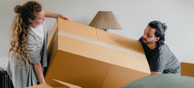a couple lifting a cardboard box