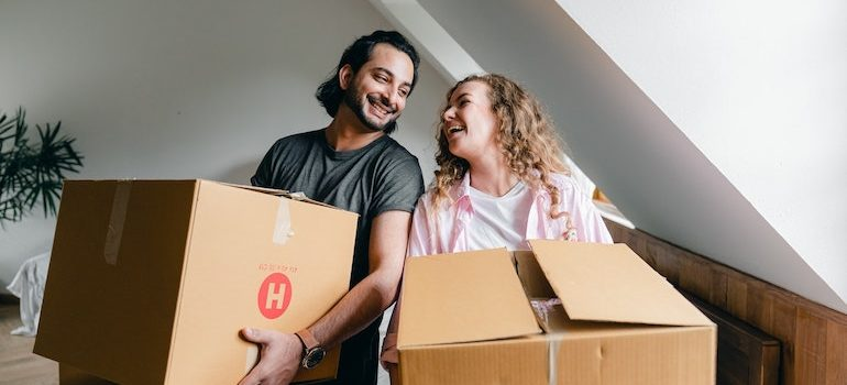 man and woman holding boxes waiting for local movers Brandon FL