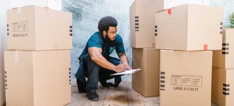 man writing on a clipboard surrounded by boxes is part of commercial movers Ocala FL