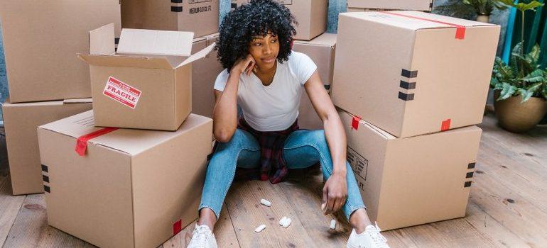woman sitting amid cardboard boxes