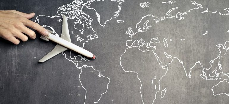person flying a model plane over a map of the world