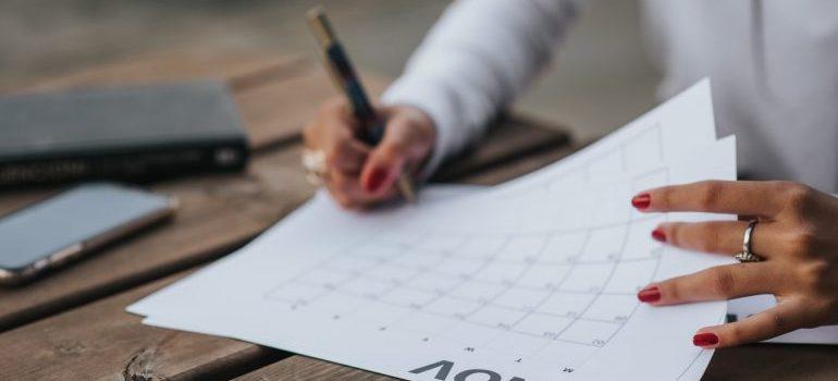 A woman browsing through a calendar.