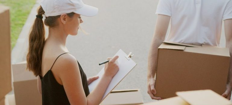 a woman taking notes while a man is carrying a box to load it into the truck