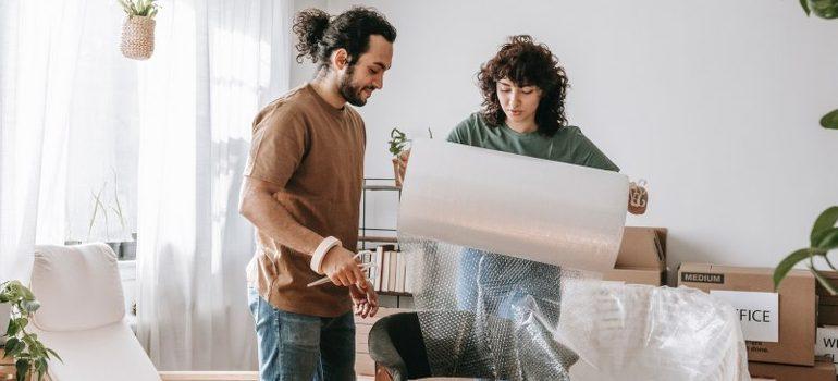 two people unrolling a sheet of bubble wrap
