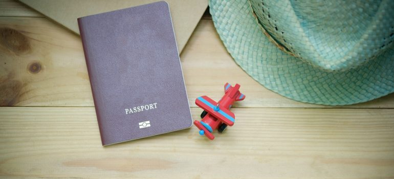 Passport, hat, and a plane toy on the table.