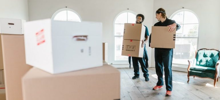 Movers carrying cardboard boxes.