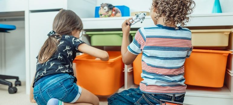 Two kids playing with toys in their room.